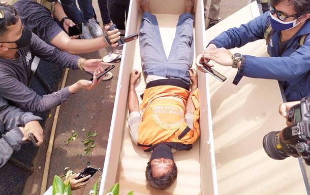 В Индонезии нарушителей карантина катают на катафалках и укладывают в гр...