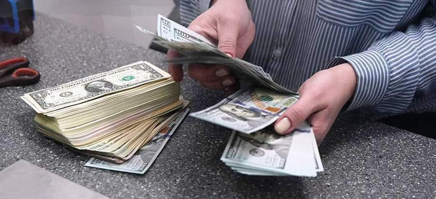 Человек пересчитывает доллары