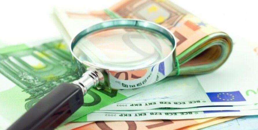 банкноты евро, лупа