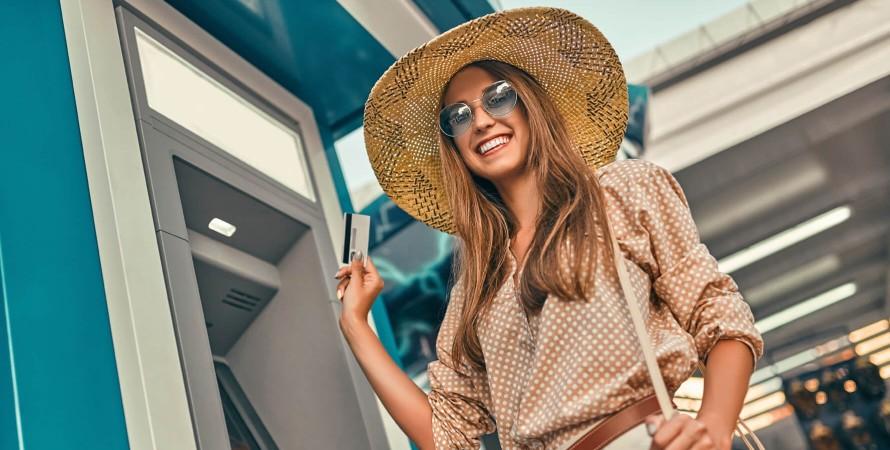девушка с банковской картой у банкомата