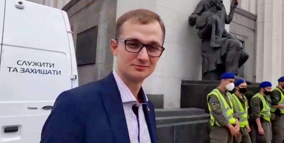 """Народний депутат від """"Слуги народу"""" Євген Брагар на тлі машини з написом """"служити і захищати"""""""